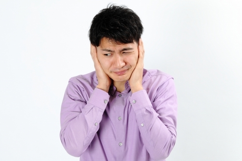 耳が痛くて押さえている男性
